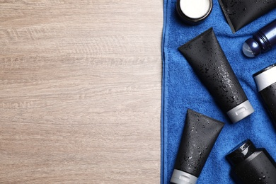Set of men's cosmetic products with blue towel on wooden table, top view. Space for text
