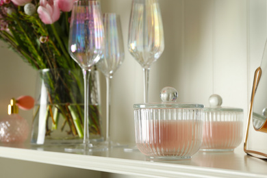 White shelving unit with glassware and different decorative elements