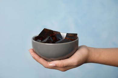 Woman holding bowl with delicious grass jelly cubes on light blue background, closeup