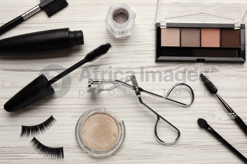Flat lay composition with eyelash curler, makeup products and accessories on white wooden table