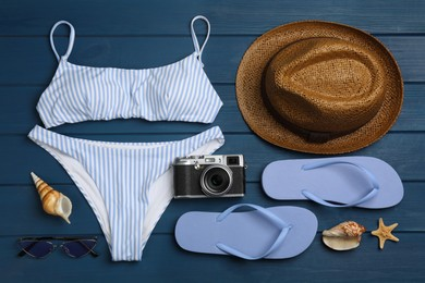 Flat lay composition with beach objects on blue wooden background