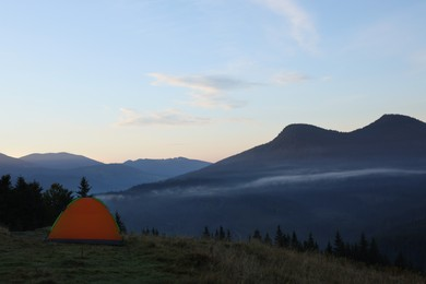 Picturesque mountain landscape with camping tent in morning