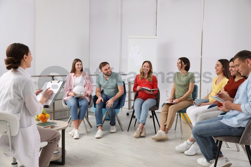 Group of pregnant women with men and doctor at courses for expectant parents indoors