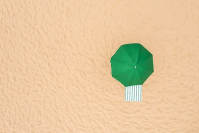 Green beach umbrella and towel on sandy coast, aerial view. Space for text