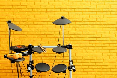 Modern electronic drum kit near yellow brick wall indoors, space for text. Musical instrument