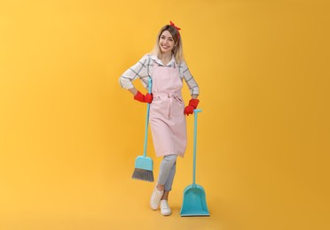 Young housewife with broom and dustpan on yellow background