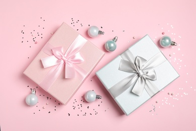 Beautiful gift boxes, Christmas balls and confetti on pink background, flat lay