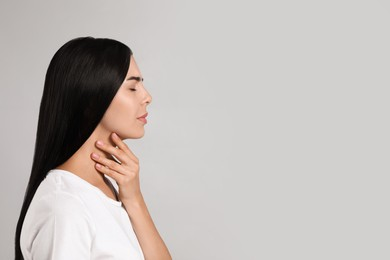 Young woman doing thyroid self examination on light background. Space for text
