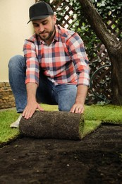 Young man laying grass sod on ground at backyard