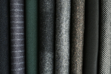 Stack of different fabric samples as background, closeup. Textile texture