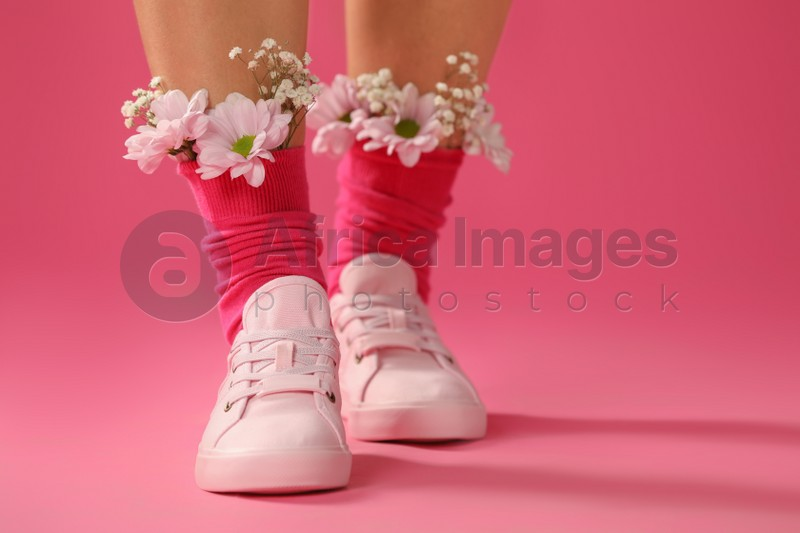 Woman with beautiful tender flowers in socks on pink background, closeup. Space for text