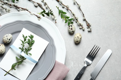 Festive Easter table setting with quail eggs on color background, flat lay
