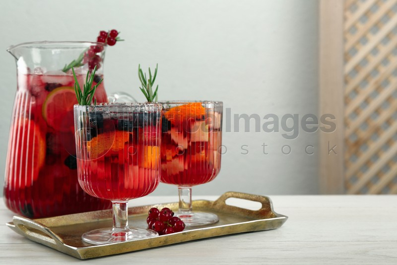Glasses and jug of Red Sangria on white wooden table