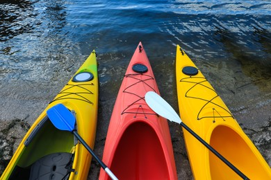 Modern kayaks with paddles on beach near river, above view. Summer camp activity