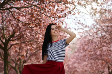 Pretty young woman wearing trendy clothes near beautiful blossoming trees outdoors. Stylish spring look