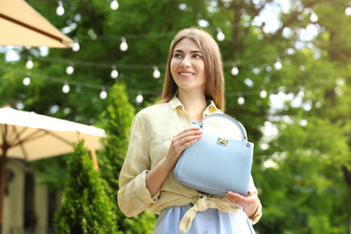 Beautiful young woman with elegant bag outdoors on summer day