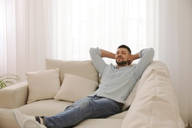Man resting on comfortable sofa in living room