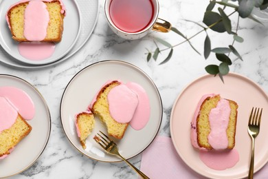 Delicious cake with pink glaze served on white marble table, flat lay
