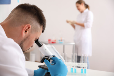Scientist using microscope at table and colleague in laboratory. Medical research