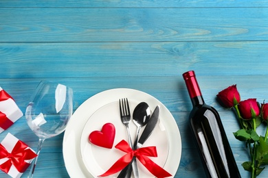 Beautiful table setting on light blue wooden background, flat lay with space for text. Valentine's Day dinner