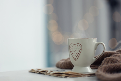 Delicious morning coffee, newspaper and knitted sweater on white table indoors. Space for text