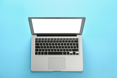 Modern laptop with blank screen on light blue background, top view