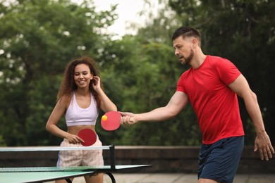 Friends playing ping pong outdoors on summer day