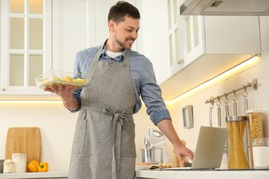 Man making dinner while watching online cooking course via laptop in kitchen