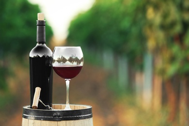 Bottle and glass of red wine on wooden barrel in vineyard