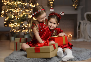 Cute little children with Christmas gifts in living room