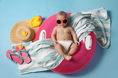 Cute little baby in sunglasses with inflatable ring and beach accessories on light blue background, top view