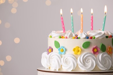 Delicious birthday cake with party decor on stand against blurred festive lights, closeup. Space for text