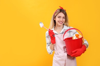 Young housewife with bucket of household items and brush on yellow background. Space for text