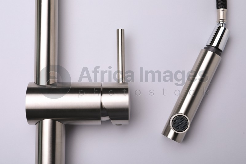 Modern pull out kitchen faucet on grey background, top view