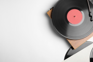 Modern vinyl record player with disc on white background, top view