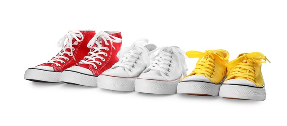 Many different sneakers on white background. Trendy shoes