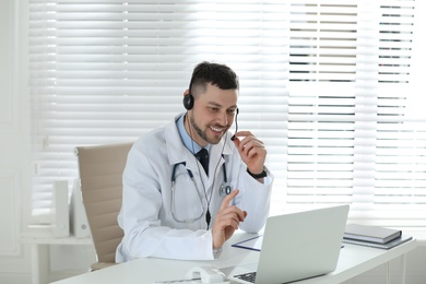 Doctor with headset consulting patient online at desk in clinic. Health service hotline