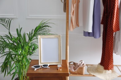 Empty photo frame, sunglasses and watch on wooden table indoors