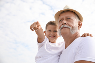 Grandfather with little boy outdoors in summer