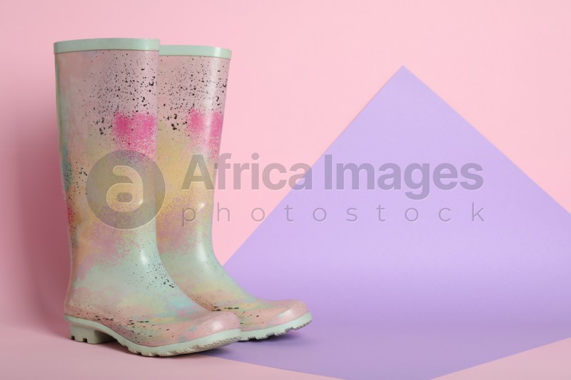 Pair of rubber boots on color background. Space for text