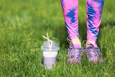 Young woman in sportswear with plastic cup of healthy smoothie on grass outdoors
