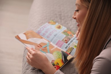 Happy woman reading magazine on bed indoors