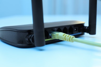 Connected cable to router on white table, closeup. Wireless internet communication