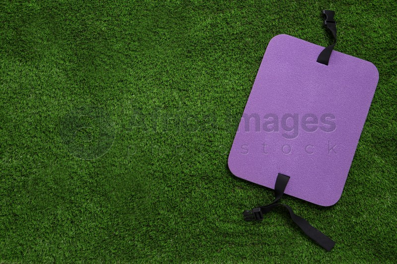 Violet foam tourist seat mat on green grass, top view. Space for text
