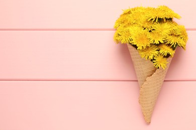 Beautiful yellow dandelions in waffle cone on pink wooden table, top view. Space for text
