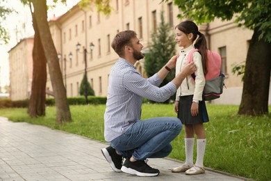 Father helping little daughter to put on school bag outdoors