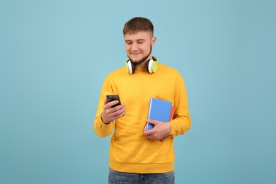 Young student with headphones and books using smartphone on light blue background