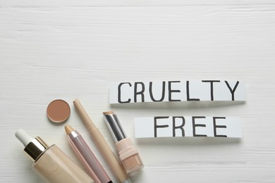 Flat lay composition with words Cruelty Free and different cosmetic products not tested on animals against white wooden background