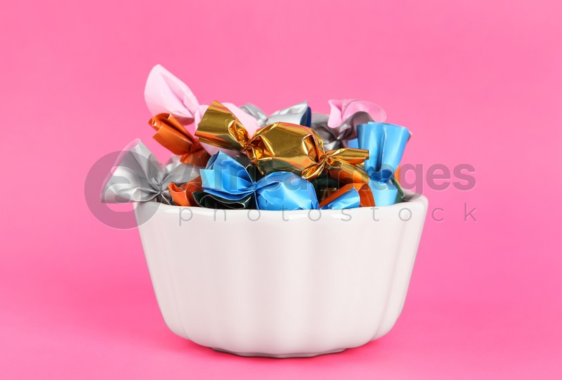 Candies in colorful wrappers on pink background, closeup