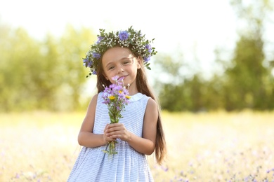 Cute little girl wearing beautiful wreath with bouquet of wildflowers outdoors. Child spending time in nature